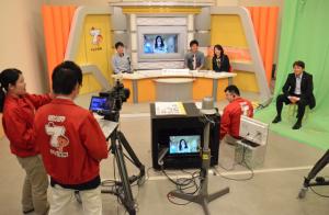 テレビ局パビリオンでは、外のインタビューの様子を生中継し ながら番組が進行していた