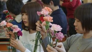 ときに談笑しながら花束をつくる生徒たち。