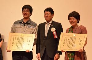 受賞した2人と笑顔で記念撮影する文部科学大臣政務官の樋口尚也氏。